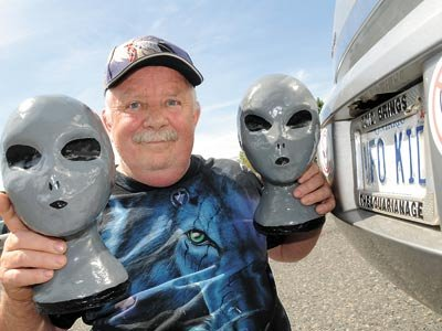 "Lorne Johnson poses with his two hand-made ""grey ET"" mannequins, next to his UFO KID license plate. The former Inco employee has been researching extraterrestrial life for nearly four decades. Photo by Marg Seregelyi"