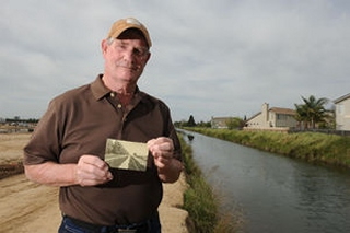John Callahan poses by the canal at Lower Sacramento Road and Lodi Avenue in Lodi on Friday, March 20, 2015, with a photograph of the area from around the time when there was an alleged alien sighting and attempted abduction of Colonel H.G. Shaw and his friend Camille Spooner in 1896.